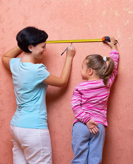 Young woman and little girl with measuring tape